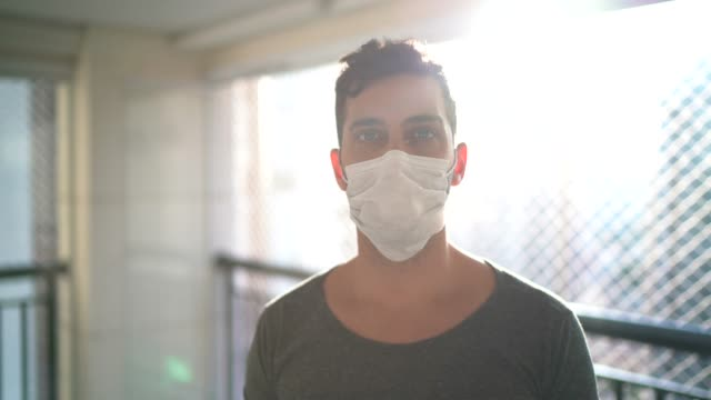portrait of a young man wearing face mask at home - prevenzione delle malattie video stock e b–roll