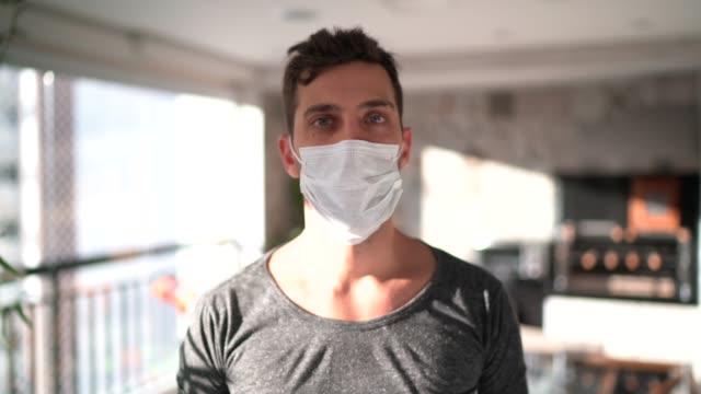 vidéos et rushes de verticale d'un jeune homme utilisant le masque de visage à la maison - confinement