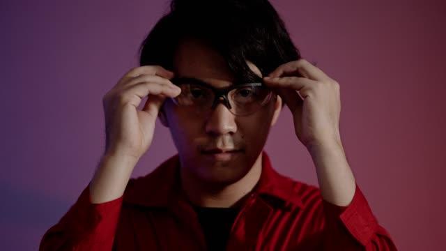 vidéos et rushes de verticale d'un jeune homme utilisant des lunettes protectrices travaillant dans l'industrie - apprenti