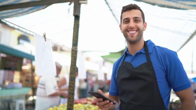 vídeos de stock e filmes b-roll de portrait of a young man working in a street market using smartphone - vendedor trabalho no comércio