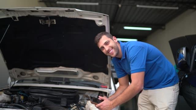 vidéos et rushes de verticale d'un jeune mécanicien fixant la voiture avec le capot ouvert - capot de voiture