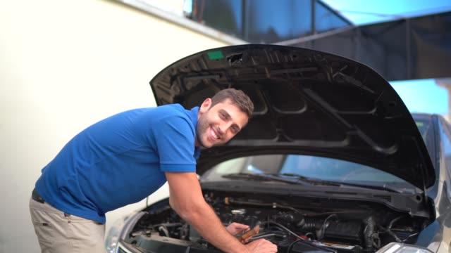 vídeos y material grabado en eventos de stock de retrato de un joven mecánico fijando coche con capucha abierta - inclinar