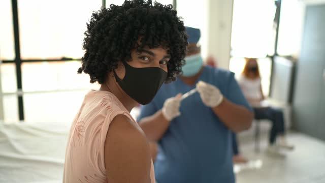 stockvideo's en b-roll-footage met portret van een jonge mensen die vaccin nemen - dat gezichtsmasker draagt - mouw