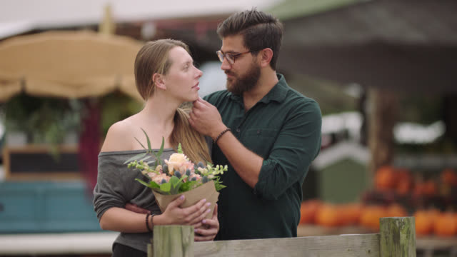 portrait of a young millennial couple at a farmer's market on an autumn day - i love you stock videos & royalty-free footage