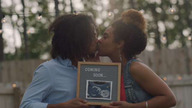portrait of a young mixed race couple announcing pregnancy during photo shoot - announcement message stock videos & royalty-free footage