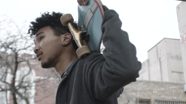 vídeos de stock e filmes b-roll de portrait of a young, mixed race skateboarder. - cultura jovem