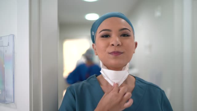 portrait of a young nurse woman taking face mask off and smiling at hospital - removing stock videos & royalty-free footage