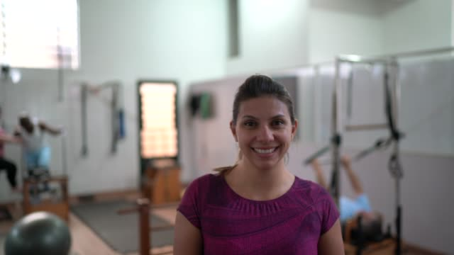 portrait of a young physiotherapy woman instructor in clinic - yoga studio stock videos & royalty-free footage