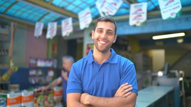 porträt eines jungen verkäufers, der in einem lackiergeschäft steht - verkäufer stock-videos und b-roll-filmmaterial