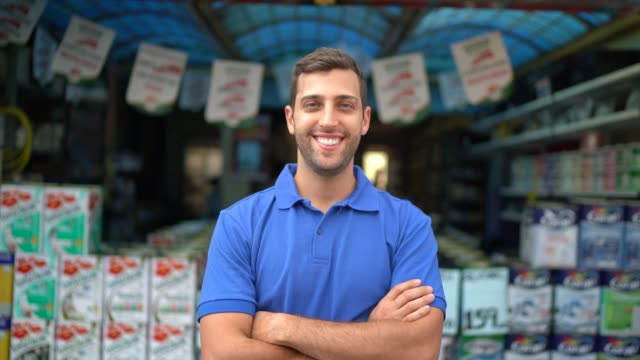 portrait of a young sales man standing in a paint store - white collar worker stock videos & royalty-free footage