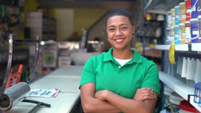 vídeos de stock, filmes e b-roll de retrato de uma mulher nova das vendas que está com os braços cruzados em uma loja da pintura - dedicação