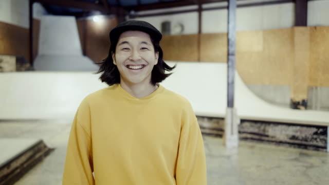 ritratto di un giovane skateboarder giapponese sorridente nello skate park (slow motion) - fashion show video stock e b–roll