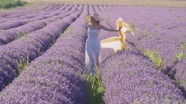 stockvideo's en b-roll-footage met portret van een jonge glimlachende tiener kleedde zich in wit in het midden van de bloeiende lavendelgebieden. wanderlust. - hoofddeksel