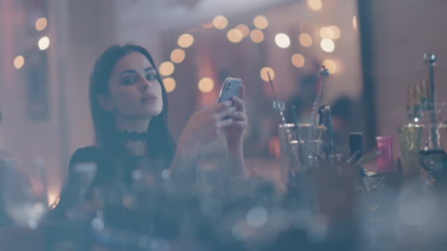 portrait of a young snobby woman sitting alone at a bar using her phone - adult stock videos & royalty-free footage