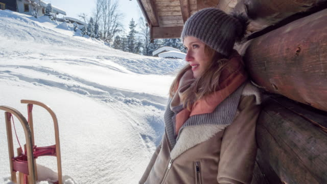 vídeos de stock e filmes b-roll de portrait of a young woman at a log cabin in winter - cabana de madeira