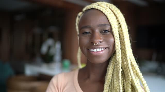 vídeos de stock e filmes b-roll de portrait of a young woman at home - cabelo natural