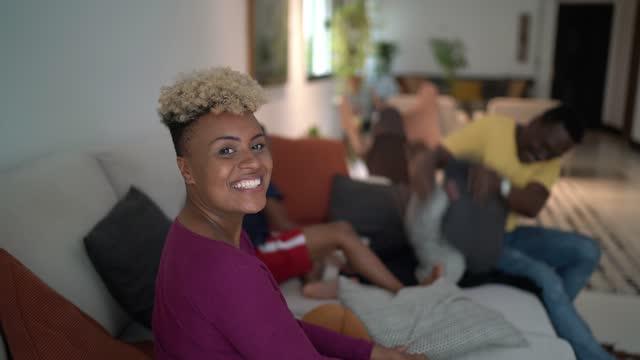 vídeos de stock, filmes e b-roll de retrato de uma jovem em casa com a família se divertindo ao fundo - cabelo encaracolado