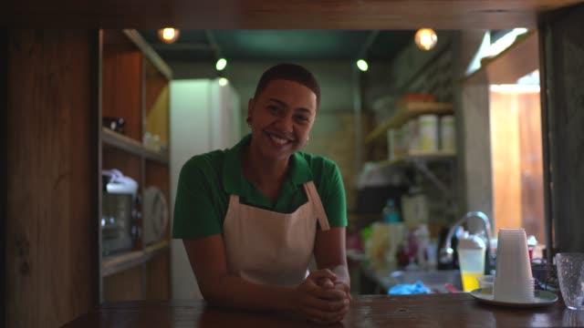 porträt einer jungen frau hinter der küchentheke eines restaurants - gastwirt stock-videos und b-roll-filmmaterial