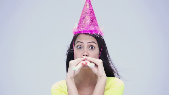 portrait of a young woman blowing party horn - party hat stock videos & royalty-free footage