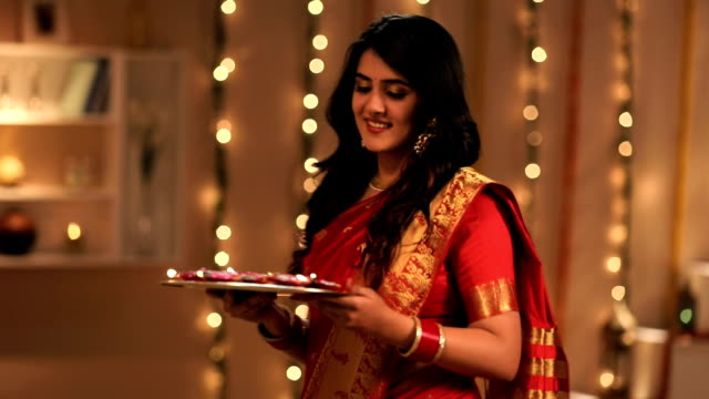 portrait of a young woman celebrating diwali festival in the home, delhi, india - sari stock videos and b-roll footage