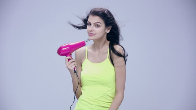 portrait of a young woman drying her long hair - blow drying hair stock videos and b-roll footage