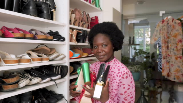 portrait of a young woman in front of her shoe collection - collezione video stock e b–roll