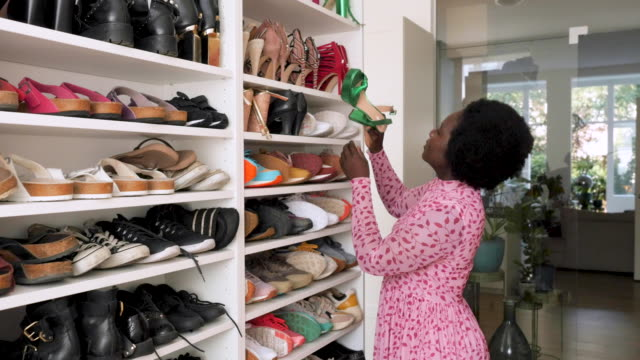 stockvideo's en b-roll-footage met portrait of a young woman in front of her shoe collection - verzameling