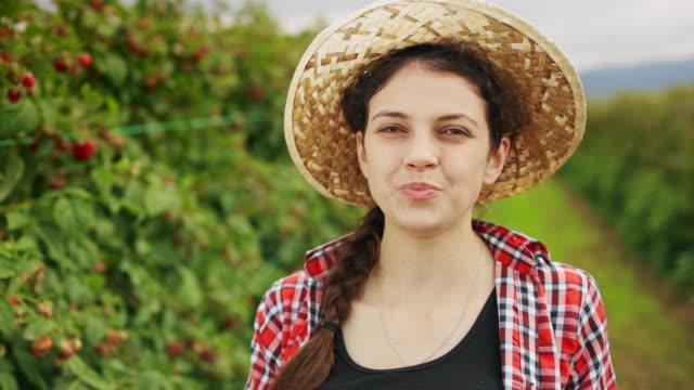 stockvideo's en b-roll-footage met portret van een jonge vrouw op een frambozenplantage op een warme en zonnige de zomerdag - strohoed