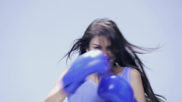 Portrait of a young woman playing boxing