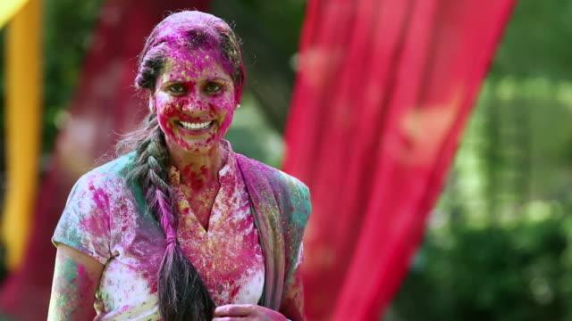 portrait of a young woman playing holi, delhi, india - 民族衣装点の映像素材/bロール