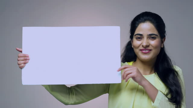 Portrait of a young woman pointing finger towards a message board