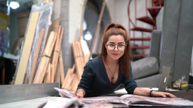 vídeos de stock, filmes e b-roll de retrato de uma mulher nova que lê um catálogo em uma oficina de upholstery - empreendedor