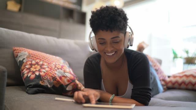 vídeos de stock, filmes e b-roll de retrato de uma mulher nova que usa a tabuleta digital e que escuta a música no sofá - música