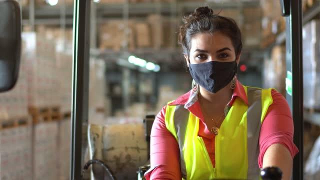 vídeos de stock e filmes b-roll de portrait of a young woman using face mask driving a forklift in a warehouse - trabalhador de armazém