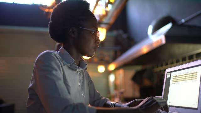 ritratto di una giovane donna che usa il laptop in un ristorante - remote control video stock e b–roll