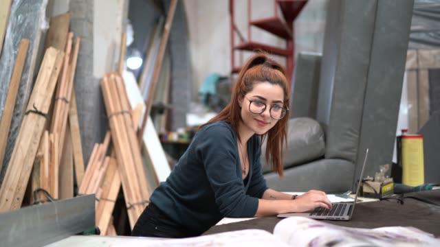 vídeos de stock e filmes b-roll de portrait of a young woman using laptop in an upholstery workshop - artigo de decoração