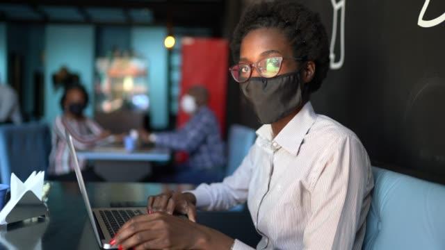 vídeos de stock, filmes e b-roll de retrato de uma jovem usando uma máscara facial protetora e usando um laptop em um restaurante - afro
