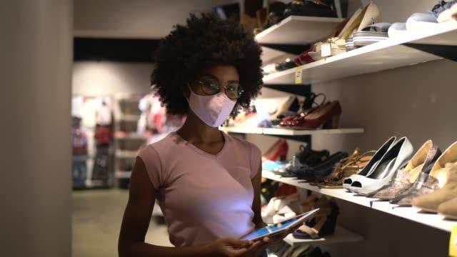 vídeos y material grabado en eventos de stock de retrato de una joven que usa máscara facial y usa una tableta digital trabajando en una zapatería - lista de chequeo