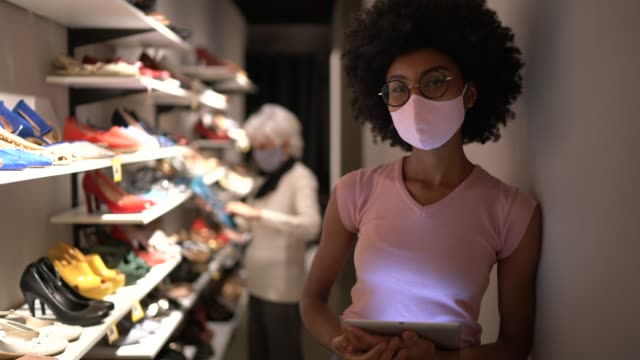 portrait of a young woman wearing face mask and using digital tablet working in a shoe store - retail occupation stock videos & royalty-free footage