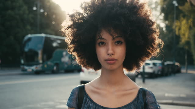 portrait of a young woman with afro hair in the city at sunset - sorridere video stock e b–roll