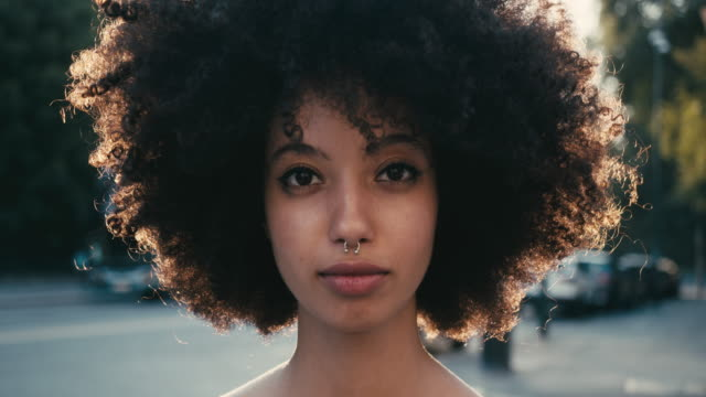 vídeos de stock e filmes b-roll de portrait of a young woman with afro hair in the city at sunset - looking at camera