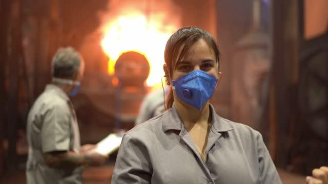 工場で働く若い女性の肖像画、炉の前に立つ - 状態点の映像素材/bロール