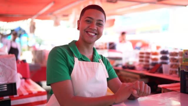 vídeos de stock, filmes e b-roll de retrato de uma mulher nova que trabalha em um mercado de rua - feirante