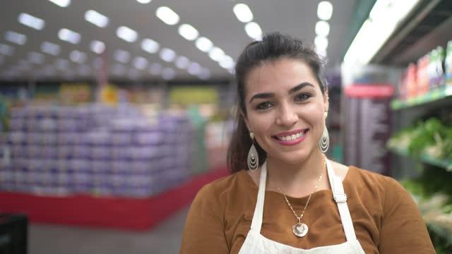 vídeos de stock, filmes e b-roll de retrato de uma jovem trabalhando em um supermercado - profissão na área de serviços