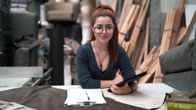 porträt einer jungen frau, die mit einem digitalen tablet in einer polsterung arbeitet - designer einrichtung stock-videos und b-roll-filmmaterial