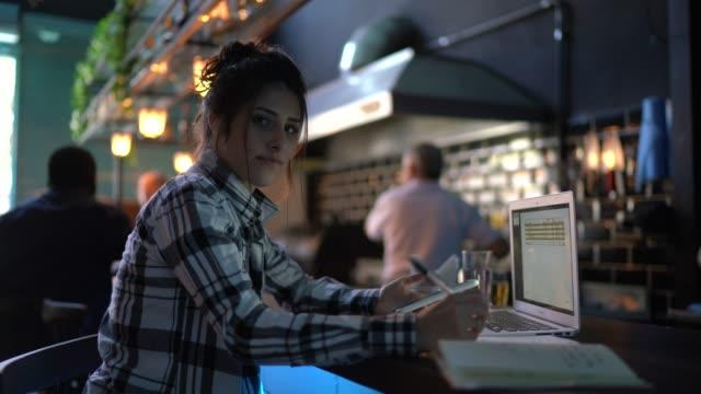 vídeos de stock, filmes e b-roll de retrato de uma jovem trabalhando ou estudando em um bar, usando laptop - trabalho de freelancer