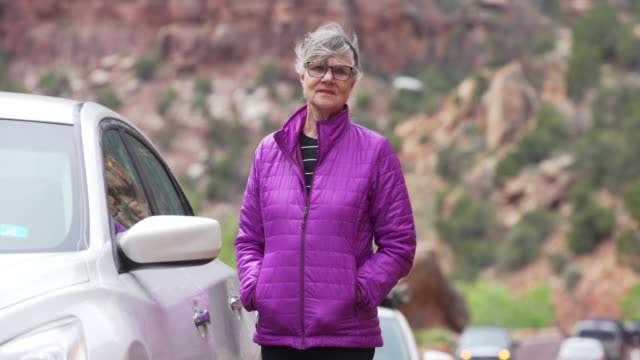 portrait of active mature woman standing next to parked car on road - next to stock videos and b-roll footage
