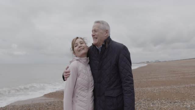 portrait of active senior adult couple day in life, on beach together in autumn - wintermantel stock-videos und b-roll-filmmaterial
