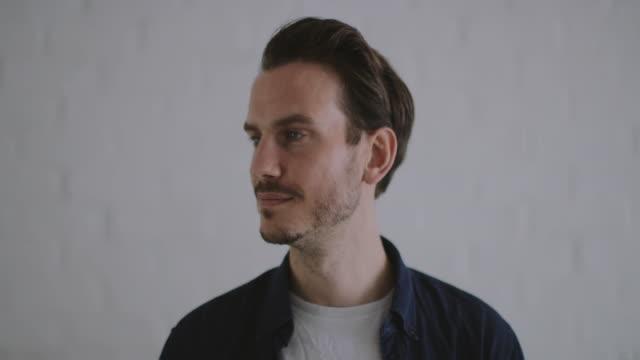 vídeos de stock e filmes b-roll de portrait of adult male against white brickwall - retrato formal