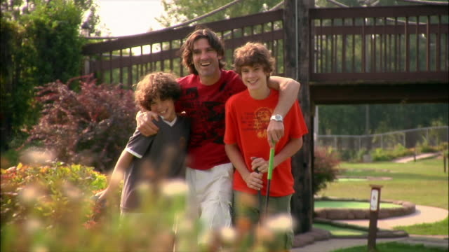 portrait of affectionate father and sons standing on mini golf course / holding golf clubs and waving - minigolf stock-videos und b-roll-filmmaterial